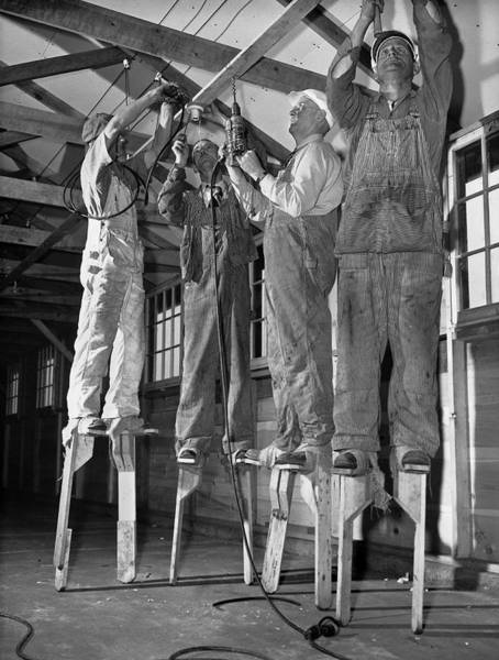 Raising Wall Art - Photograph - Electricians On Stilts by Underwood Archives