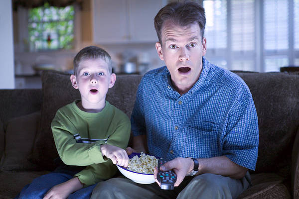 Father And Son With Remote Control And Popcorn Art Print by Thinkstock Images