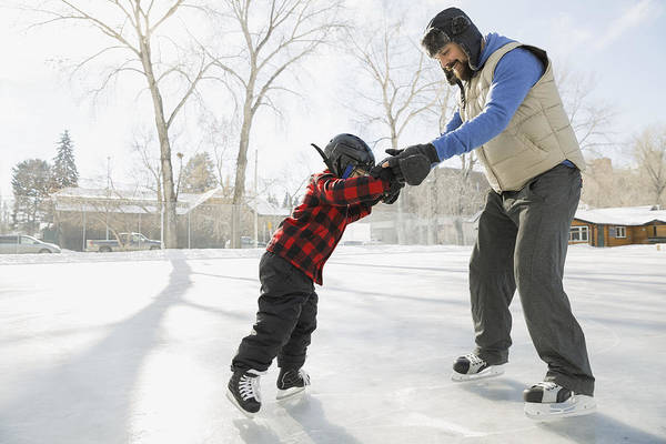 Father Teaching Son To Ice-skate On Outdoor Rink Art Print by Hero Images
