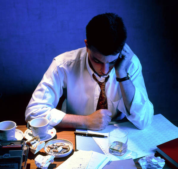 Depression Photograph - Fatigued Businessman Sitting At His Desk At Night by Sheila Terry/science Photo Library