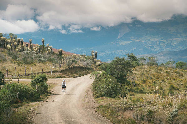 Boyaca Photograph - Female Cyclist Riding Along Gravel Road by Brent Olson