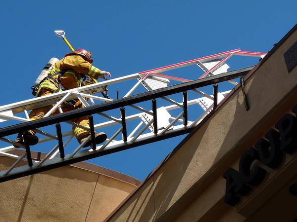 Photograph - Firefighter Climbing Ladder by Jeff Lowe
