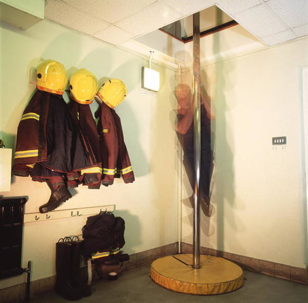Wall Art - Photograph - Firefighter Sliding Down Pole by Simon Lewis/science Photo Library