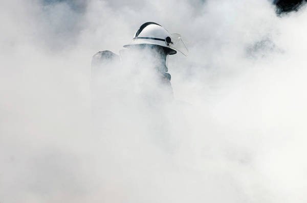 Firemen Photograph - Fireman Extinguishing A Fire by Jim Varney/science Photo Library