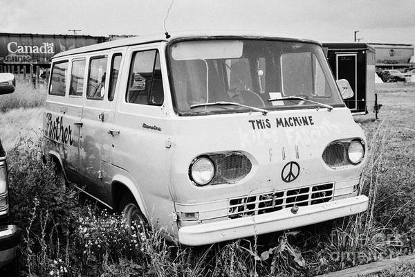 Ford Van Photograph - first generation ford econoline camper van with hippy symbols in a junkyard Saskatchewan Canada by Joe Fox