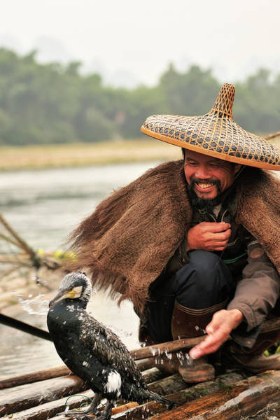 Chinese Clothing Wall Art - Photograph - Fisherman And His Cormorant On Li River by Huang Xin