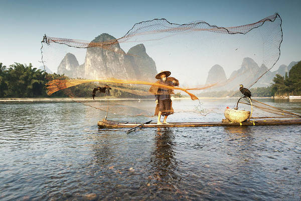 Chinese Clothing Wall Art - Photograph - Fisherman On Bamboo Boat Throwing The by Matteo Colombo