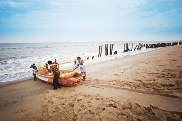 Pulling Photograph - Fishermen Pulling A Boat Into The Sea by Exotica.im