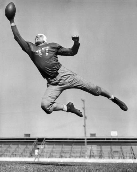 Jumping Photograph - Football Player Catching Pass by Underwood Archives