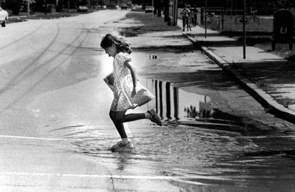 Wall Art - Photograph - Girl Playing In A Puddle by Retro Images Archive