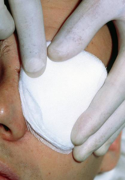 Bandage Photograph - Gloved Fingers Apply Dressing To Patient's Eye by Garry Watson/science Photo Library