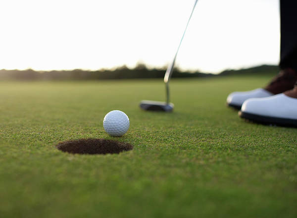 Senior Adult Photograph - Golf Ball At Edge Of Hole On Green by Dougal Waters