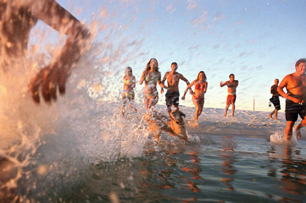 Group Of Young Adults Running Through Water At Ocean's Shore Art Print by Sean Murphy