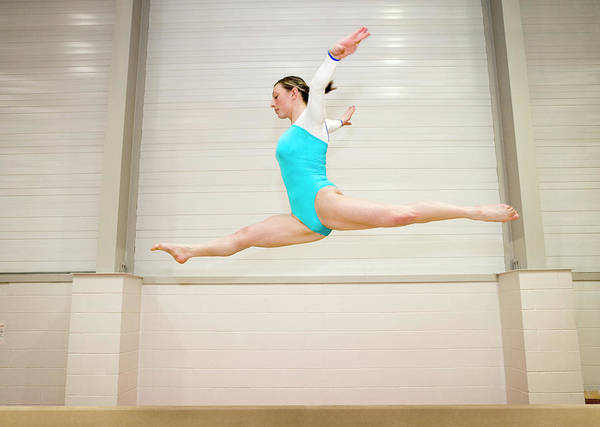 Agile Photograph - Gymnast Jumping On A Balance Beam by Gustoimages/science Photo Library