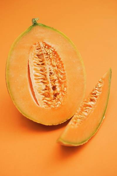 Wall Art - Photograph - Half A Cantaloupe Melon With Slice Of Melon by Foodcollection