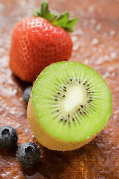 Kiwifruit Photograph - Half A Kiwi Fruit, Blueberries And Strawberry by Foodcollection