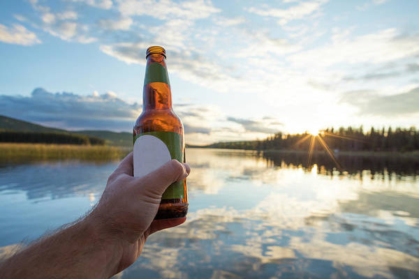 Wall Art - Photograph - Hand Holding Beer Bottle Against Lake by Christopher Kimmel