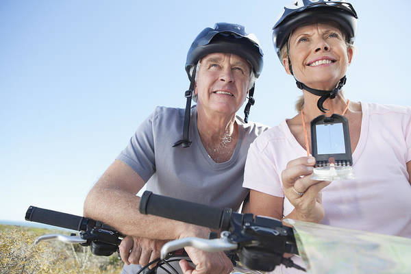 Happy Mature Woman Mountain Biking With Man Using Gps Art Print by OJO Images