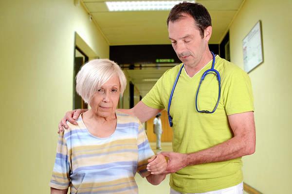 Corridor Photograph - Hospital Doctor Assisting Elderly Woman by Aj Photo