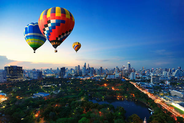Hot Air Balloons Fly Over Cityscape At Sunset Background Art Print by Busakorn Pongparnit