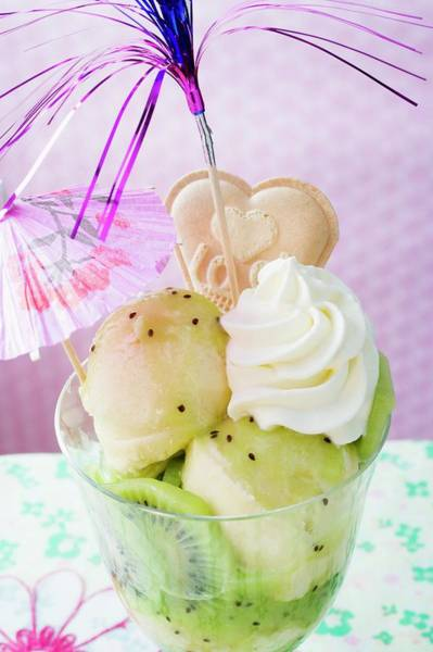 Kiwifruit Photograph - Ice Cream Sundae With Kiwi Fruit, Cream And Cocktail Umbrella by Foodcollection