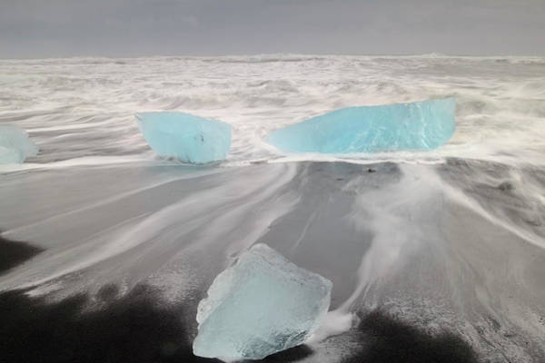 Storm Photograph - Icebergs Washed Up On Volcanic Sandy by Travelpix Ltd
