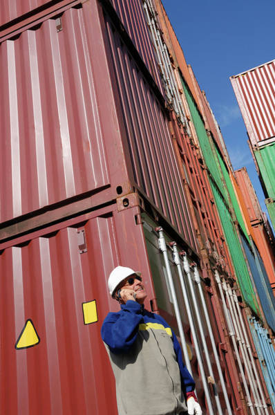 Wall Art - Photograph - Industrial Worker On Cell Phone With Cargo Containers by Christian Lagerek/science Photo Library