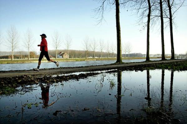 Riverside Photograph - Jogging by Christophe Vander Eecken/reporters/science Photo Library