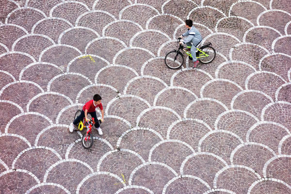 Casual Photograph - Kids Riding Bikes In Small Square Over by Ben Miller