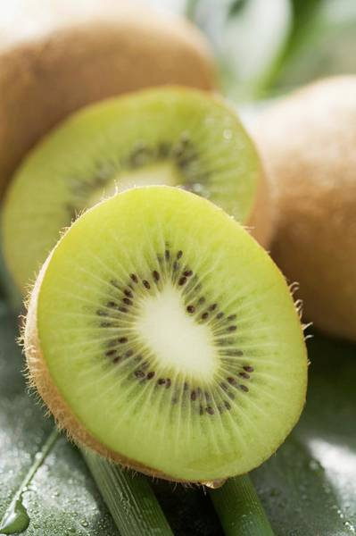 Kiwifruit Photograph - Kiwi Fruit, Whole And Halved by Foodcollection