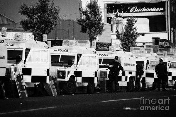 Turmoil Photograph - Line Of Psni Landrovers And Officers On Crumlin Road At Ardoyne Shops Belfast 12th July by Joe Fox