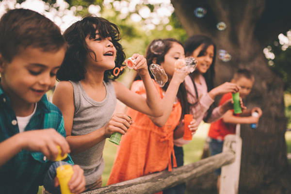 Little Boy Having Fun With Friends In Park Blowing Bubbles Art Print by Wundervisuals