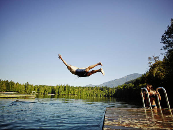 Candid Photograph - Man Diving Off Dock Into Mountain Lake by Thomas Barwick