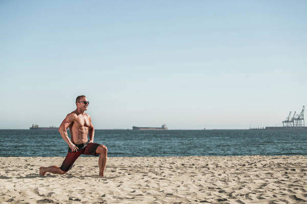 Wall Art - Photograph - Man Doing Lunges On Beach by Fat Tony