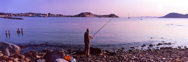 Elba Photograph - Man Fishing At The Coast, Portoferraio by Panoramic Images