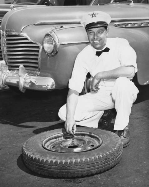 Wall Art - Photograph - Man Fixing A Flat Tire by Underwood Archives