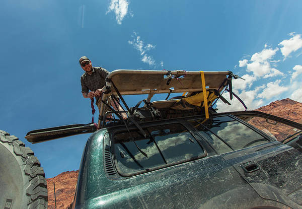 Top Gear Wall Art - Photograph - Man On Top Of Vehicle Unloading Gear by Scott Hardesty