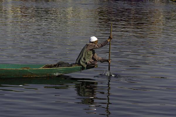Dal Lake Photograph - Man Plying A Wooden Boat On The Dal Lake by Ashish Agarwal