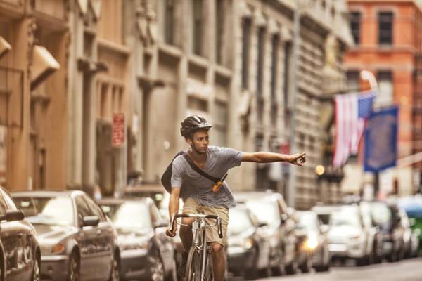 Man Riding Bicycle On City Street Art Print by Sam Edwards