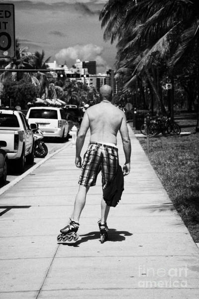 Roller Blades Photograph - Man Rollerblading Along Ocean Drive Early Morning Art Deco District Miami South Beach Florida Usa by Joe Fox