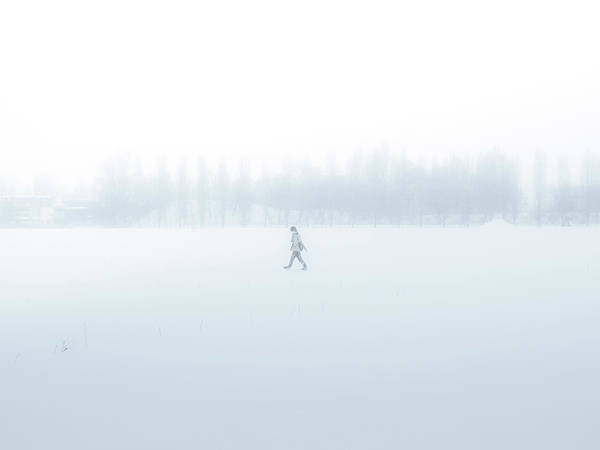 Snowfield Photograph - Man Walking Through A Snowfield by Taketan