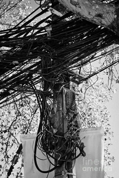 Cabling Photograph - messy open telephone and electricity cables wires on pole in downtown Santiago Chile by Joe Fox