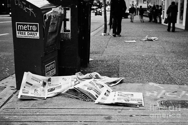 Metro Vancouver Wall Art - Photograph - metro free newspapers thrown discarded on the sidewalk Vancouver BC Canada by Joe Fox