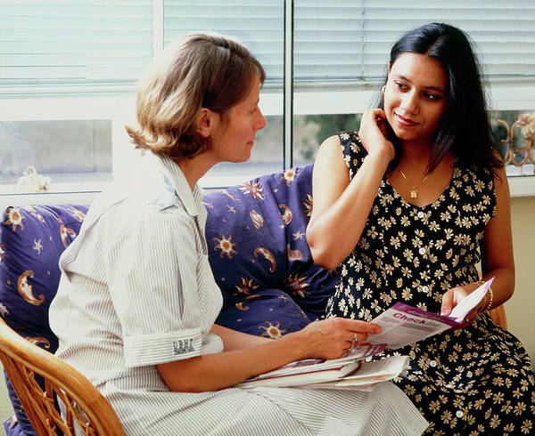 Pregnant Photograph - Midwife Talks To A Pregnant Woman On A Home Visit by Ruth Jenkinson/midirs/science Photo Library