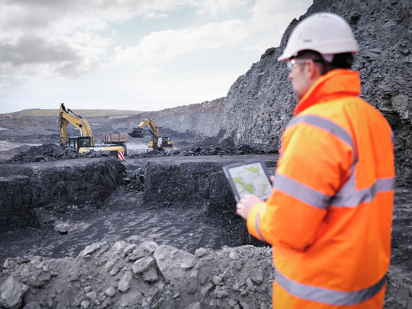 Protective Clothing Photograph - Miner Checks Plans On Digital Tablet In by Monty Rakusen