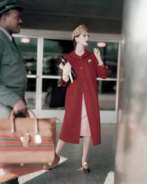 Red Coat Photograph - Model In A Red Coat At The Airport by Karen Radkai