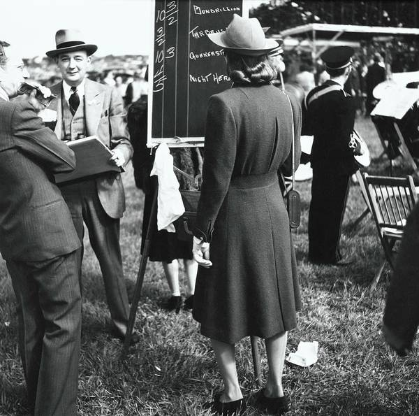 Race Horse Photograph - Model Wearing A Coat By A Scoreboard by Toni Frissell
