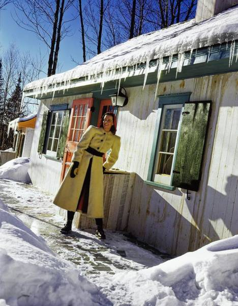 Snow Photograph - Model Wearing A Sheepskin Coat By A Winter Cottage by Toni Frissell