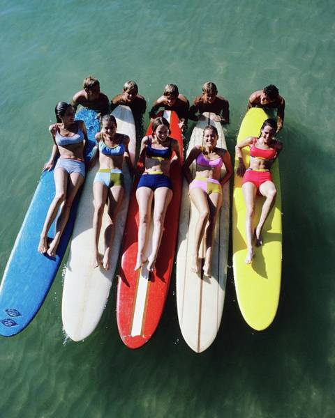 Caucasian Wall Art - Photograph - Models Wearing Bikinis Lying On Surfboards by William Connors