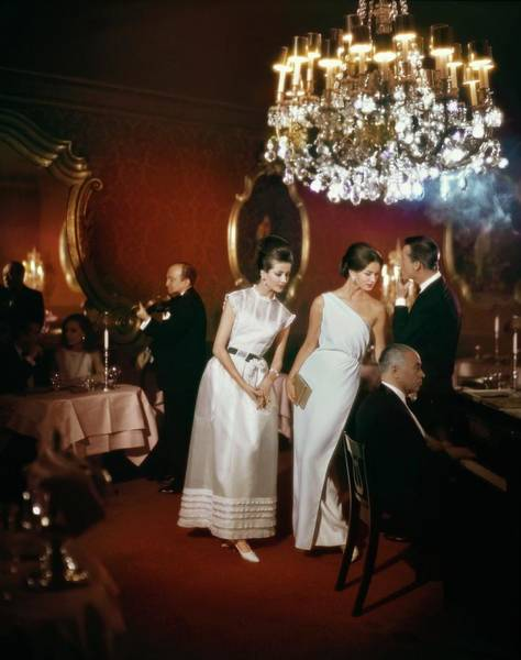 Furniture Photograph - Models Wearing Evening Gowns In El Morocco Night by John Rawlings